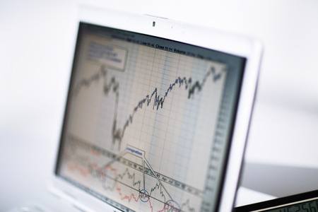 arms trade: Businessman analyzing investment charts with laptop. Accounting Stock Photo