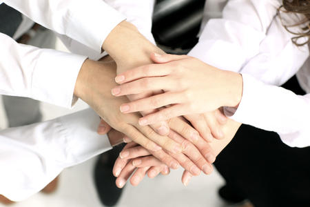 altogether: business team putting their hands on top of each other