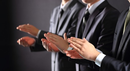 glorify: Male hands clapping on black, side-view Stock Photo
