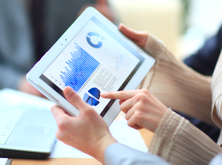 compute: Business people discussing and analyzing market data information on a modern digital tablet compute Stock Photo
