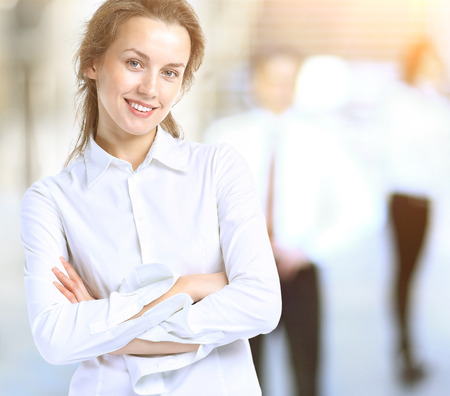 Business lady with a positive outlook and cheerful smile posing for the camera, in the background  team