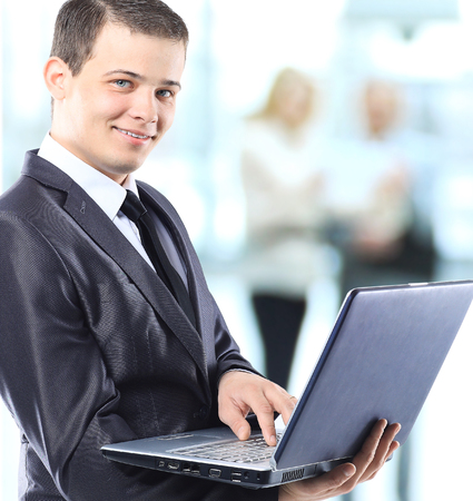 Happy smart business man with a laptop in hand on the background of team