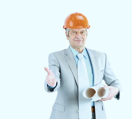 executive helmet: good engineer keeps the work plans and holds out his hand for a handshake. Stock Photo