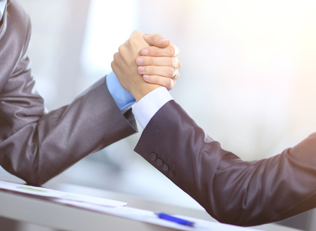 Two businessmen press hands with each other in the foreground. Fighting between entrepreneurs.