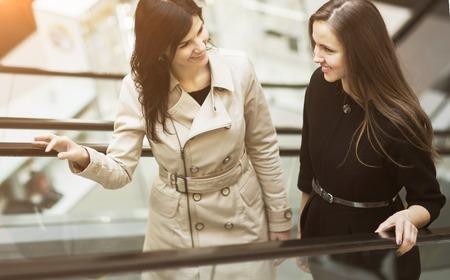 jovenes empresarios: Two business people on the escalator,  young entrepreneurs talk about work plans Foto de archivo