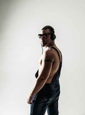 side view - the rapper shirtless with headphones and stylish hai Stock Photo