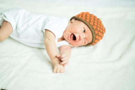 cute newborn baby beanie lying on the bed Stock Photo
