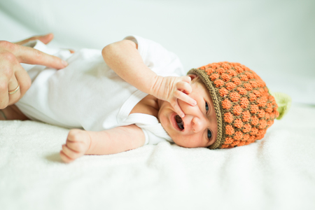 cute newborn baby in knitted hat lying Stock Photo