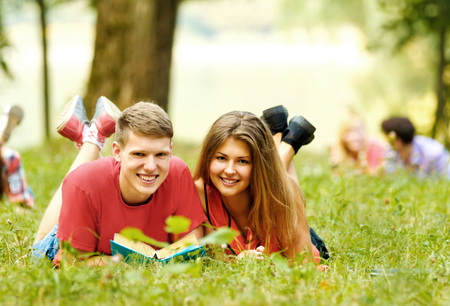 pair successful students with a textbook in a Park on a Sunny da