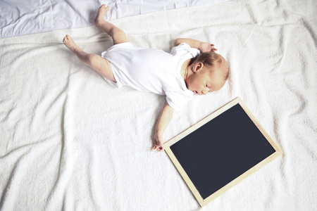 newborn baby with a greeting card lying on the sofa Stock Photo