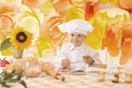 happy little boy with a book chef preparing Breakfast