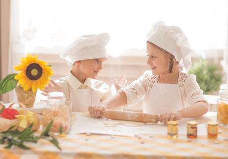 Glückliche kleine Kinder in Form eines Kochs, um köstliches Essen zuzubereiten Standard-Bild - 72798015