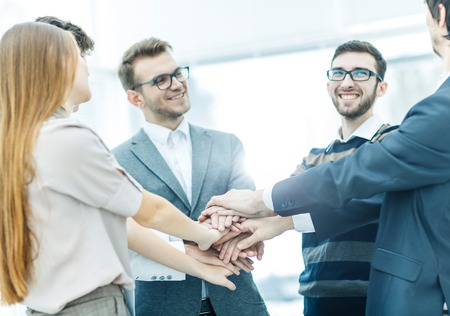 concept of success in business: friendly business team standing in a circle and joining his hands together Stock Photo