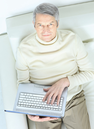 Elderly man at home with laptop on sofa looking up