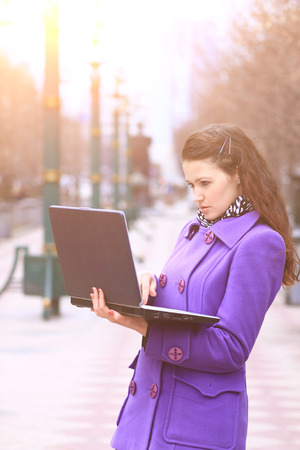 Beautiful girl with a laptop outdoors on sunny day