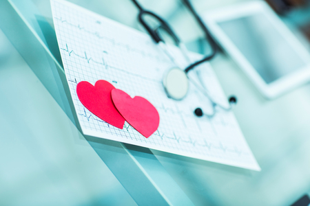 electrocardiograma: health concept: two red paper heart on the electrocardiogram, the cardiologist.