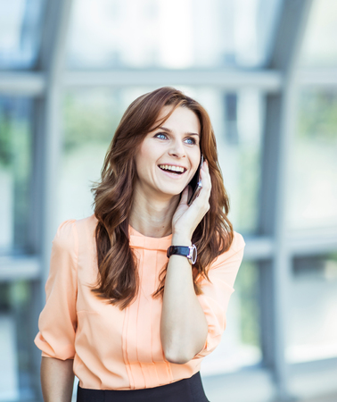 successful business woman talking on smartphone on background office