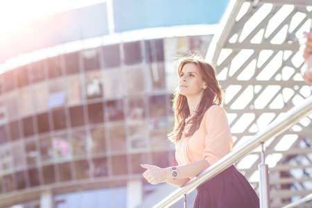 successful business woman standing on the balcony of the modern office and looks into the distance.