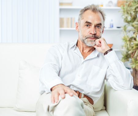 portrait of confident businessman sitting on couch in bright office.