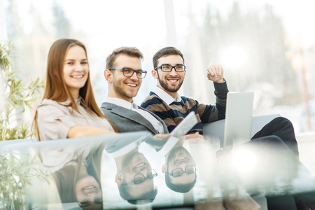 peers: employees with a laptop sitting in the lobby of the office