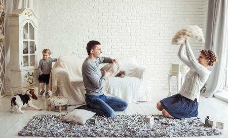 幸せな家族やペットの犬を広々 としたリビング ルームで枕で遊んで