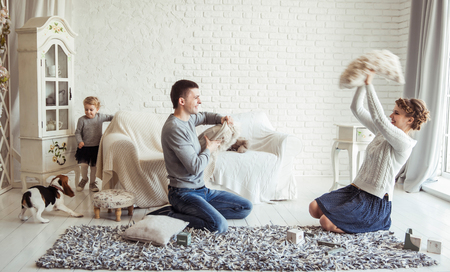 happy family and pet dog playing with pillows in spacious living room