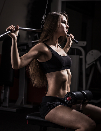 business woman doing exercise on a fitness machine in a fitness club. Stock Photo