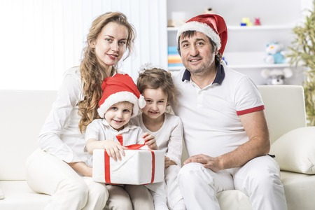 happy family with Christmas gift sitting on a sofa in the nursery. Banco de Imagens