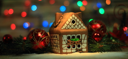 gingerbread house and Christmas decorations on festive backgrou