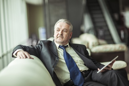 successful businessman with digital tablet sitting on the sofa in the private office