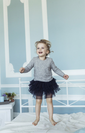 happy five year old girl jumping on the bed Stock Photo