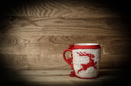 Christmas Cup with knitted ornaments on wooden background.