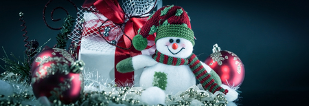 cute toy box snowman with gifts on a black background.
