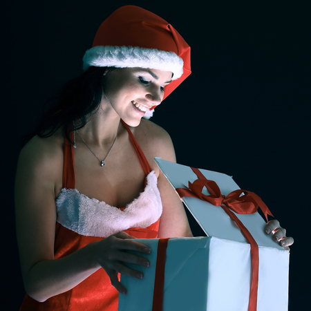 surprised young woman in costume of Santa Claus opening a Chris Stock Photo