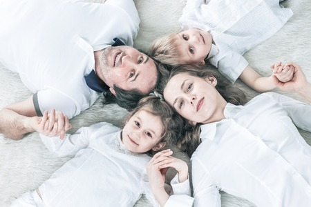 concept of family happiness: happy family relaxing on the carpet on Sunday