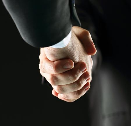 Handshake - Hand holding on black background Stock Photo