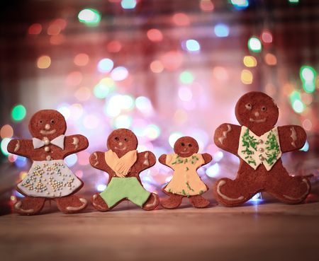 gingerbread house and gingerbread men on a festive background