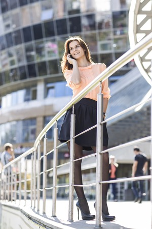 successful business woman talking on smartphone in front of a big modern office building Stock Photo