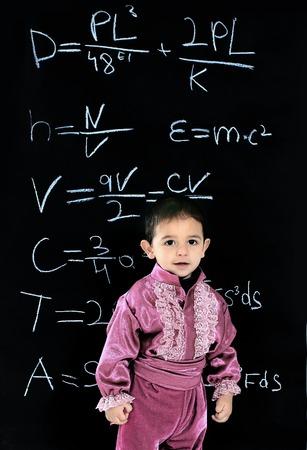 little Gypsy boy in national costume standing near school blackboard 스톡 콘텐츠