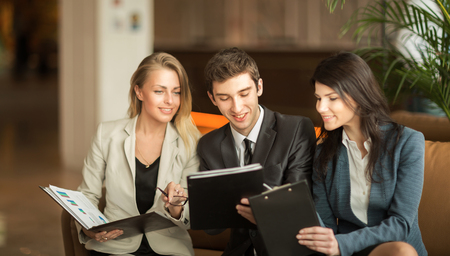 Business team discussing working papers sitting on the couch in the lobby of a modern office