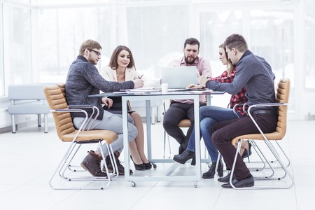 business team discussing work documents sitting behind a Desk Stock Photo