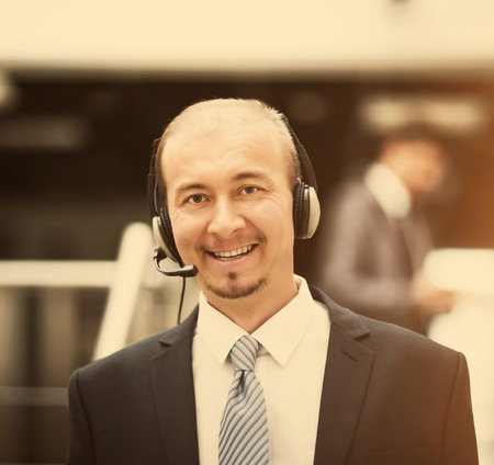 Young customer service operator talking on the headset, smiling. Stock Photo