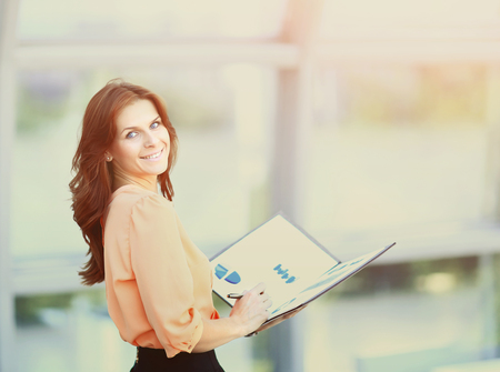 attractive business woman holding a folder with charts and diagrams in office