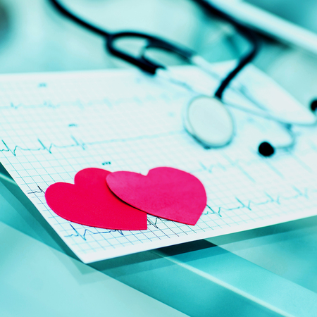 health concept: two red paper heart on the electrocardiogram, the cardiologist.
