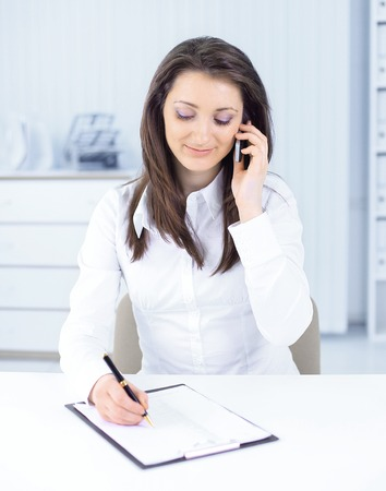 business woman discussing work documents on a mobile phone