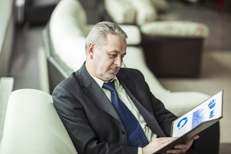 experienced financier with financial charts sitting in the chair in front of the office. Stock Photo
