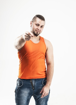 portrait of a sporty guy - bodybuilder in jeans and orange t-shi Stock Photo