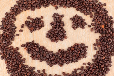 funny face of black coffee beans on wooden background Foto de archivo