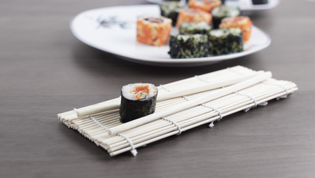sushi rolls and chopsticks on a wooden table