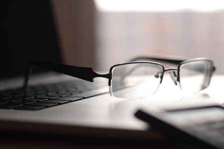 close up.glasses in black frame on the laptop keyboard.photo with copy space